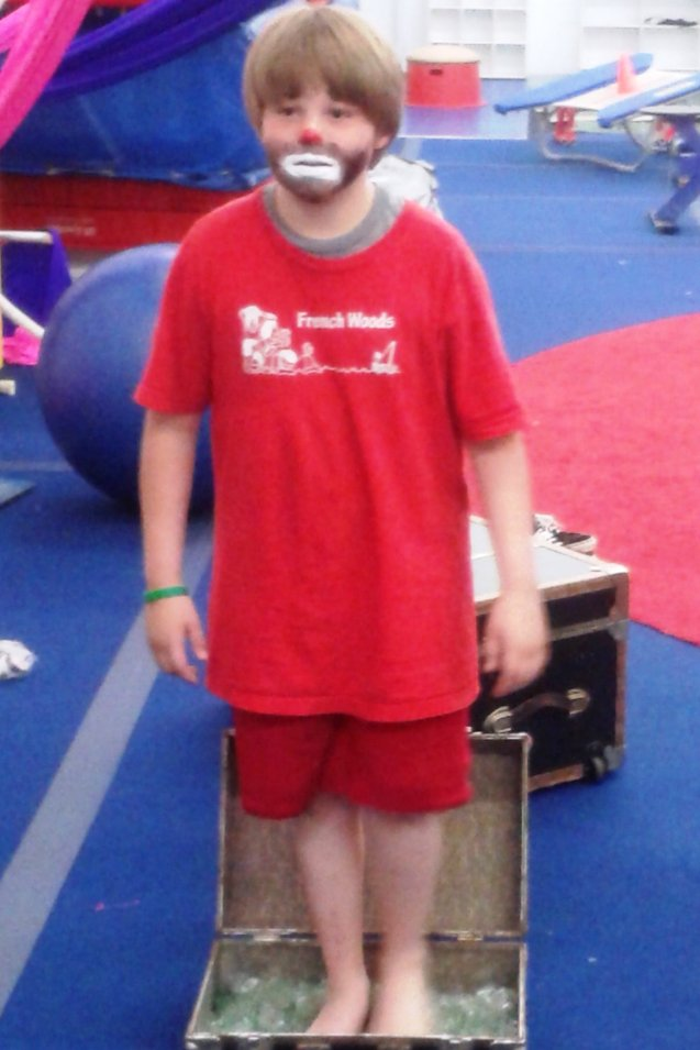 12-year-old circus performer Kameron Badgers standing on broken glass