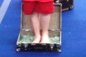 Close up of 12-year-old clown Kameron Badgers standing barefoot in broken glass