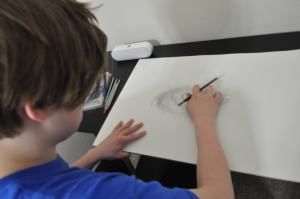 Kameron Badgers working in Jacob's sketchbook for the film Beyond the Bridge